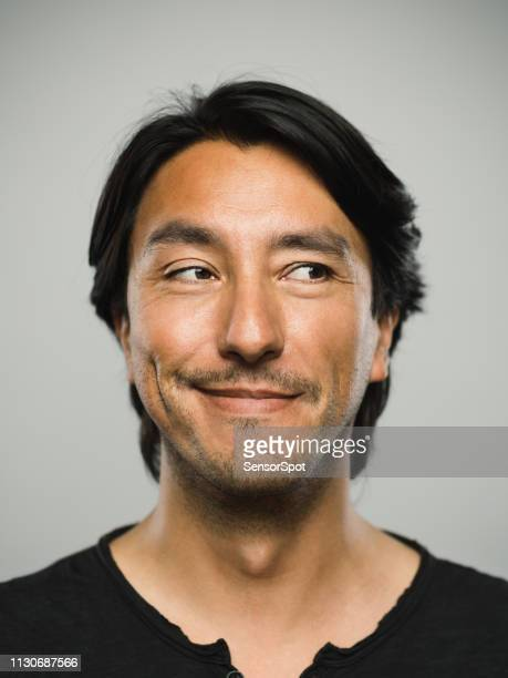 portrait of real hispanic man with happy expression looking to the side - smirking stock pictures, royalty-free photos & images