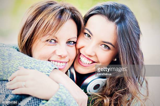 Portrait of real mother with teenage daughter outdoors