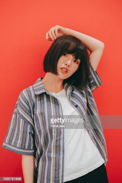 portrait of real woman on red background - asian model stock photos and pictures