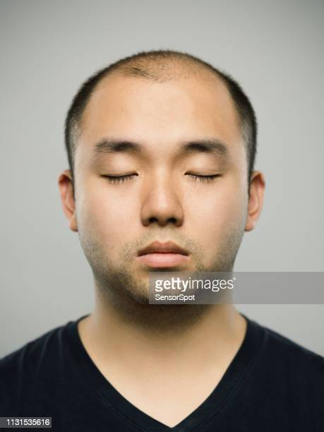 Portrait of real young adult chinese man with blank expression and eyes closed
