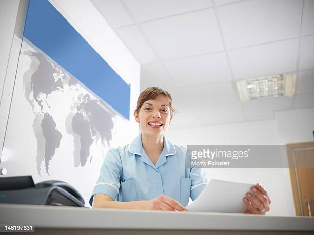 portrait of receptionist in dentist  office at desk, smiling - medical receptionist uniforms - fotografias e filmes do acervo