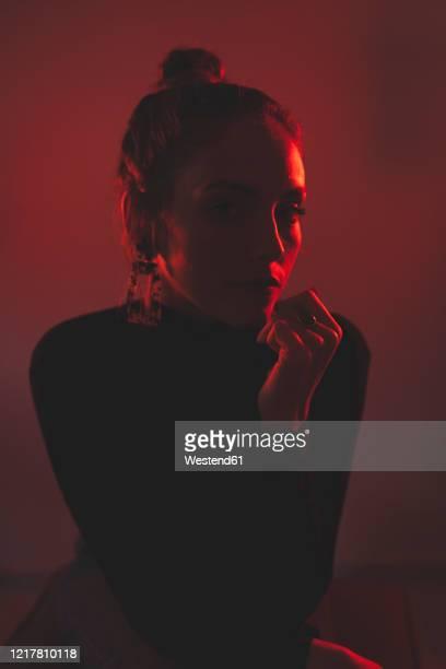 portrait of red illuminated young against red background - junge frau rätsel stock-fotos und bilder