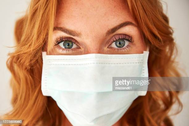 portrait of red-haired woman wearing a face mask at home - pandemic stock pictures, royalty-free photos & images