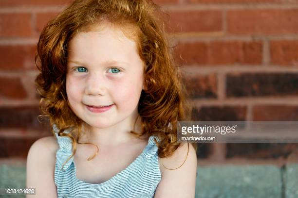 Portrait of redhead little girl outdoors on a brick wall.