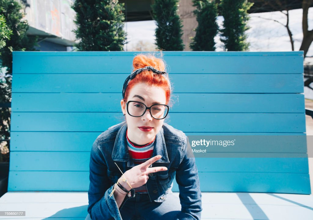 Portrait of redhead young woman gesturing peace sign while sitting on bench : Stock-Foto