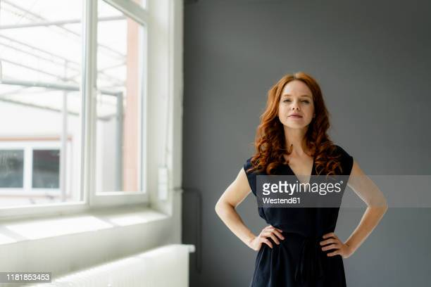portrait of redheaded businesswoman  in a loft - selbstvertrauen stock-fotos und bilder