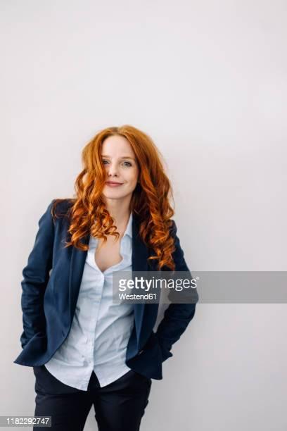 portrait of redheaded businesswoman - une seule femme d'âge moyen photos et images de collection
