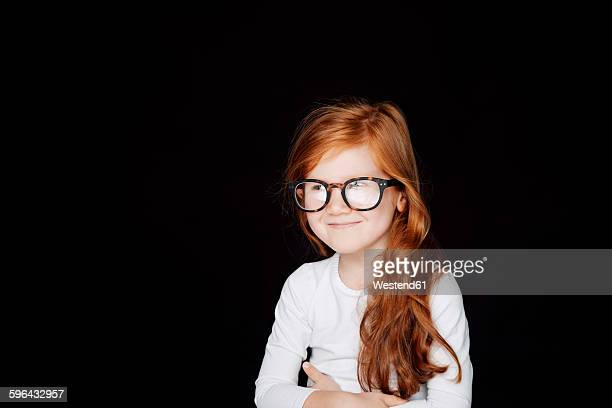 Portrait of redheaded smiling little girl wearing oversized glasses in front of black background