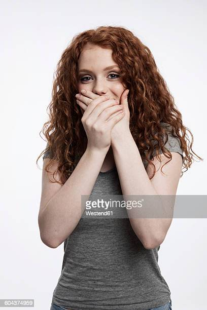 Portrait of redheaded teenage girl covering mouth with her hands