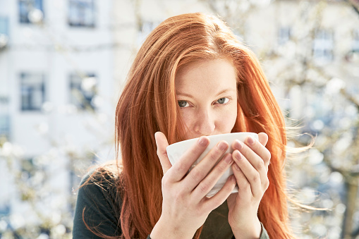 Portrait of redheaded woman drinking bowl of white coffee on balcony - gettyimageskorea