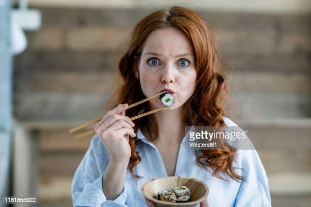 portrait of redheaded woman eating sushi - starren stock-fotos und bilder