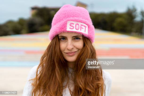 portrait of redheaded woman wearing pink cap with the word 'soft' - irony stockfoto's en -beelden