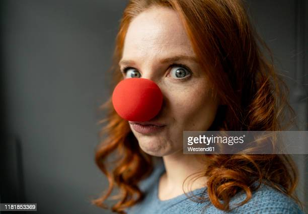 portrait of redheaded woman with clown's nose - clown stock-fotos und bilder