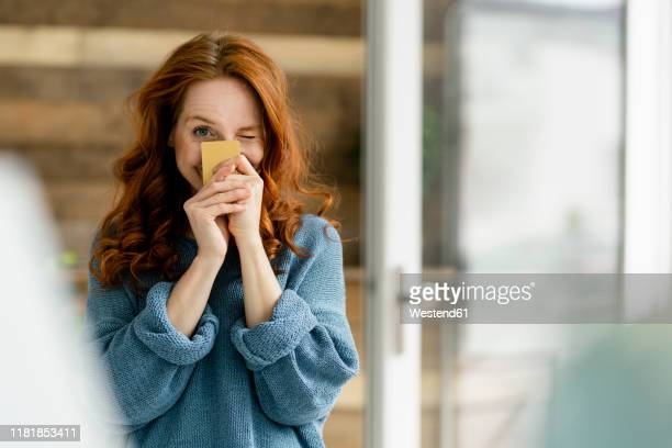 portrait of redheaded woman with credit card in a loft - ginger banks stock pictures, royalty-free photos & images
