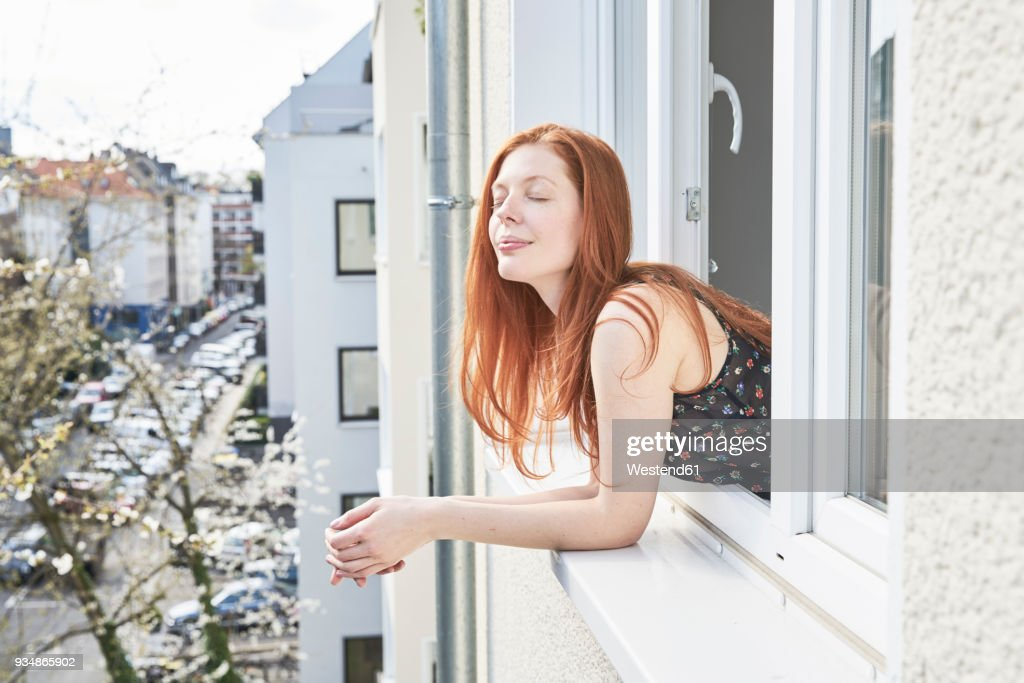 Portrait of redheaded woman with eyes closed leaning out of window : Stock-Foto