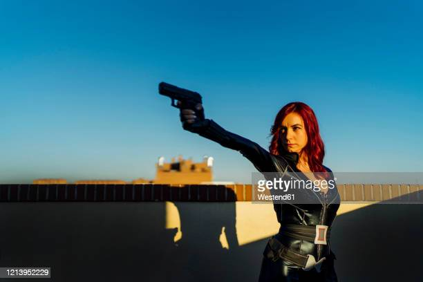 portrait of redheaded woman with gun in her hand wearing black leather catsuit on rooftop - hero and not superhero stock pictures, royalty-free photos & images