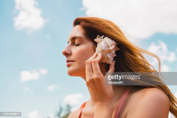 portrait of redheaded woman with mussel - hearing protection stock pictures, royalty-free photos & images