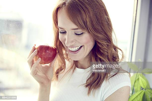 Portrait of redheaded woman with red apple