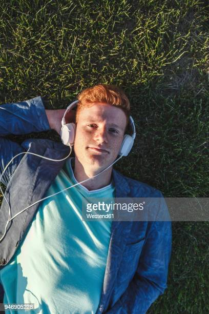 Portrait of redheaded young man with headphones lying on grass