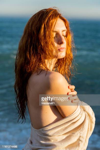portrait of redheaded young woman with nose piercing in front of the sea - off shoulder stock pictures, royalty-free photos & images