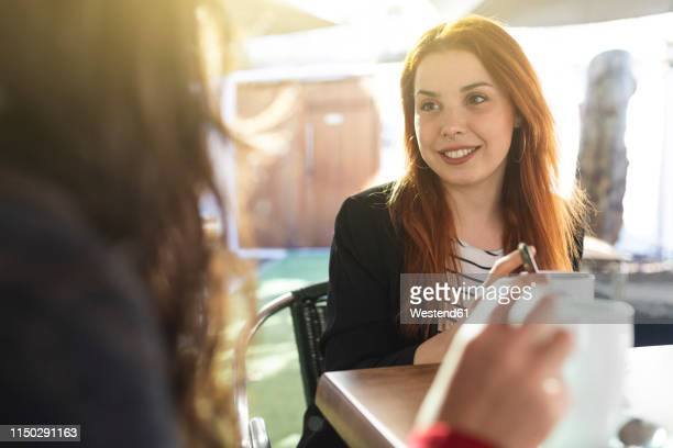 portrait of redheaded young woman with nose piercing looking at her friend at pavement cafe - amigas fotografías e imágenes de stock