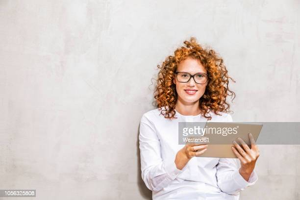 portrait of redheaded young woman with tablet - bluse stock-fotos und bilder