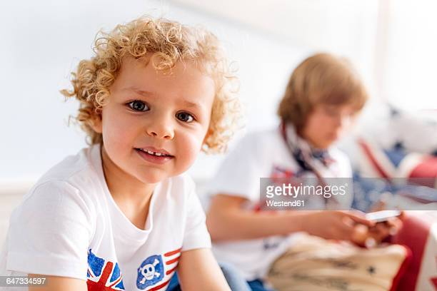 Portrait of relaxed little boy at home with his brother in the background