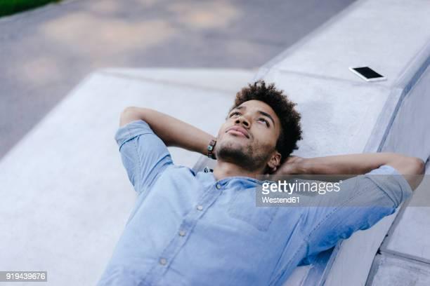 portrait of relaxed man lying in skatepark - hände hinter dem kopf stock-fotos und bilder
