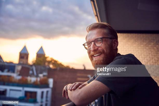 portrait of relaxed man on balcony looking at distance - mid volwassen mannen stockfoto's en -beelden