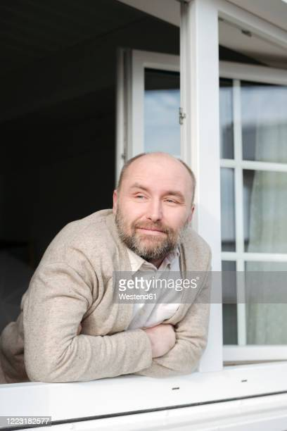 portrait of relaxed mature man leaning out of window - receding hairline stock pictures, royalty-free photos & images