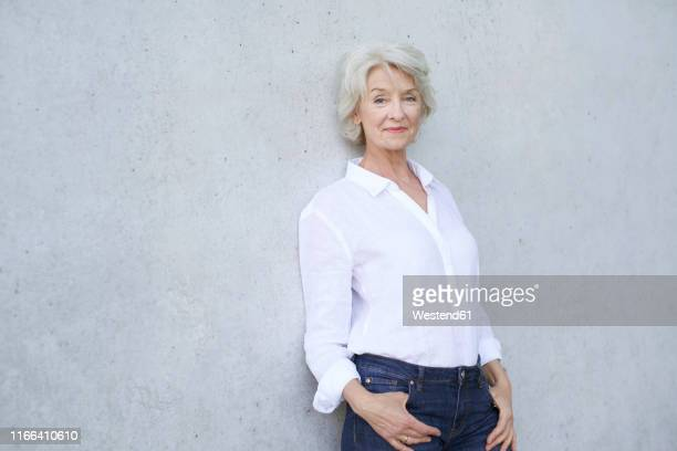 portrait of relaxed mature woman wearing white shirt leaning against concrete wall - chemisier blanc photos et images de collection
