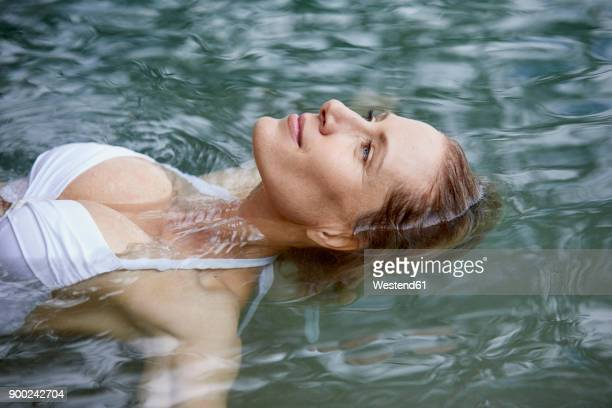 portrait of relaxed woman floating on water - auf dem wasser treiben stock-fotos und bilder
