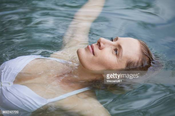 portrait of relaxed woman floating on water - erfrischung stock-fotos und bilder