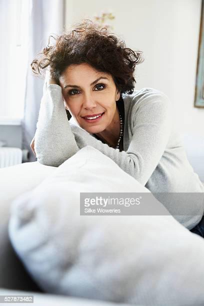 portrait of relaxed woman in living room - femme 50 ans brune photos et images de collection