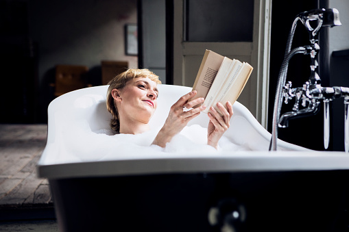 Portrait of relaxed woman taking bubble bath in a loft reading a book - gettyimageskorea