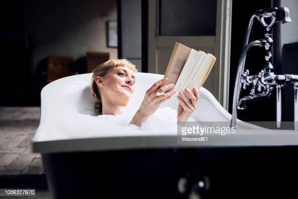 portrait of relaxed woman taking bubble bath in a loft reading a book - taking a bath stock pictures, royalty-free photos & images