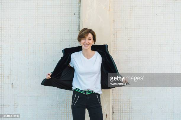 portrait of relaxed woman taking off her jacket - europese etniciteit stockfoto's en -beelden