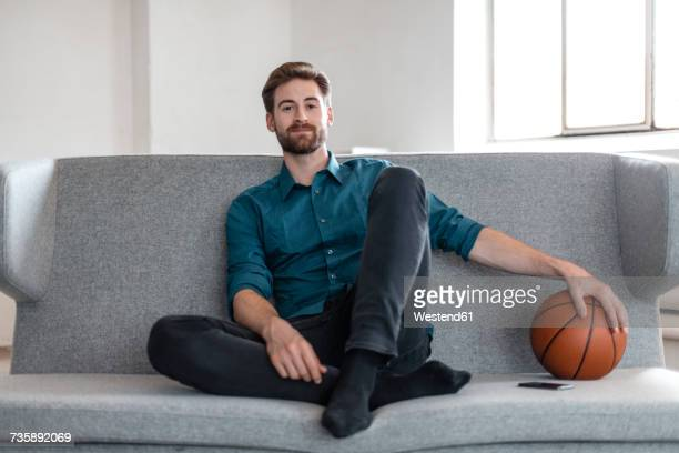 portrait of relaxed young man sitting on couch with basketball - sitzen stock-fotos und bilder