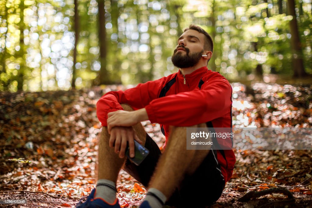 Portrait of relaxed young man with bluetooth headphones in forest : Stock Photo