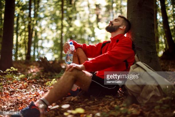 森の中でブルートゥースヘッドフォンを持つリラックスした若者の肖像画 - 心の健康 ストックフォトと画像