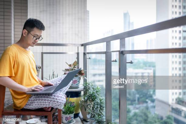 portrait of relaxed young man with laptop sitting on terrace - borough district type stock pictures, royalty-free photos & images