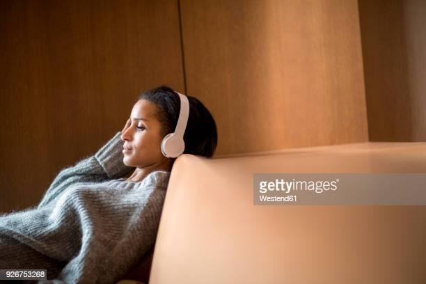 portrait of relaxed young woman listening music with headphones on couch - bank zitmeubels stockfoto's en -beelden