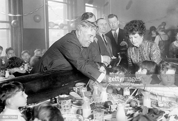 Portrait of reputed gangster Joseph 'Diamond Joe' Esposito standing in a room full of children sitting at tables covered with plates of food and milk...