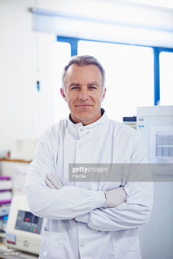 Portrait of researcher standing in lab wearing lab coat : Stock Photo