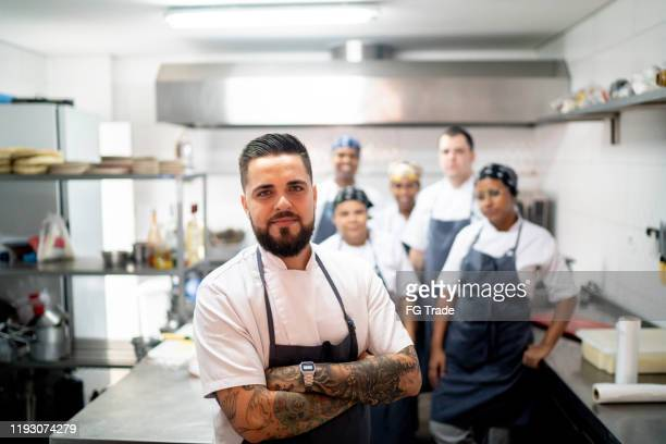 Portrait of restaurant chef with his team in the kitchen