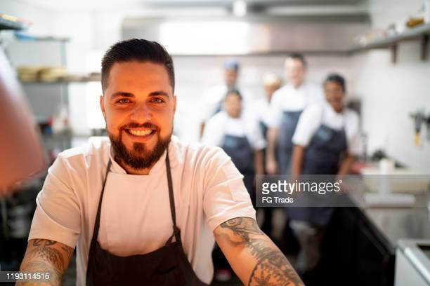 portrait of restaurant chef with his team in the kitchen - medium group of people stock pictures, royalty-free photos & images