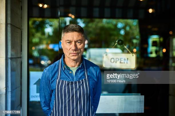 portrait of restaurant owner outside door - part of a series stock pictures, royalty-free photos & images