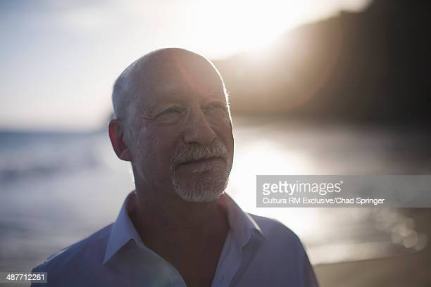 Portrait of retired businessman on beach at sunset