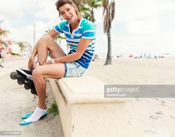 "portrait of retired trans woman putting on roller skates near beach. - ""martine doucet"" or martinedoucet bildbanksfoton och bilder"