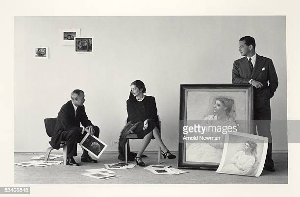 Portrait of Roland L Redmond Mrs G Macculloch Miller and John Hay Whitney three Museum of Modern Art trustees as they pose with an assortment of...